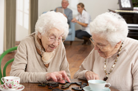 senior women playing dominoes at day care center